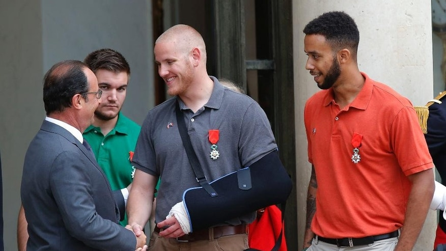 CORRECTS SADLER'S SCHOOL TO SACRAMENTO STATE UNIVERSITY, INSTEAD OF SACRAMENTO UNIVERSITY - French President Francois Hollande bids farewell to U.S. Airman Spencer Stone as U.S. National Guardsman Alek Skarlatos of Roseburg, Ore., second from left, and Anthony Sadler, a senior at Sacramento State University in California, right, look on at the Elysee Palace in Paris, France, after Hollande awarded them with the French Legion of Honor on Monday, Aug. 24, 2015. The three American travelers say they relied on gut instinct and a close bond forged over years of friendship as they took down a heavily armed man on a passenger train speeding through Belgium on Friday, Aug. 21. (AP Photo/Michel Euler)