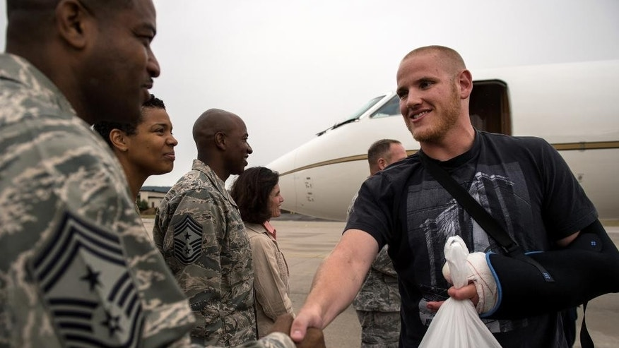 In this Aug. 24, 2015 picture, provided by U.S, Airforce Ramstein ,  Air Force Airman 1st Class Spencer Stone , right, meets Chief Master Sgt. Phillip Easton, 86th Airlift Wing command chief, upon his arrival to Ramstein Air Base, Germany. Stone, along with childhood friends Aleksander Skarlatos and Anthony Sadler, was recently honored by French President François Hollande with the French Legion of Honour for subduing an armed gunman when he entered their train carrying an assault rifle, a handgun and a box cutter. Stone is an ambulance service technician with the 65th Medical Operations Squadron stationed at Lajes Field, Azores. (Staff Sgt. Sara Keller/U.S. Air Force via AP) MANDATORY CREDIT