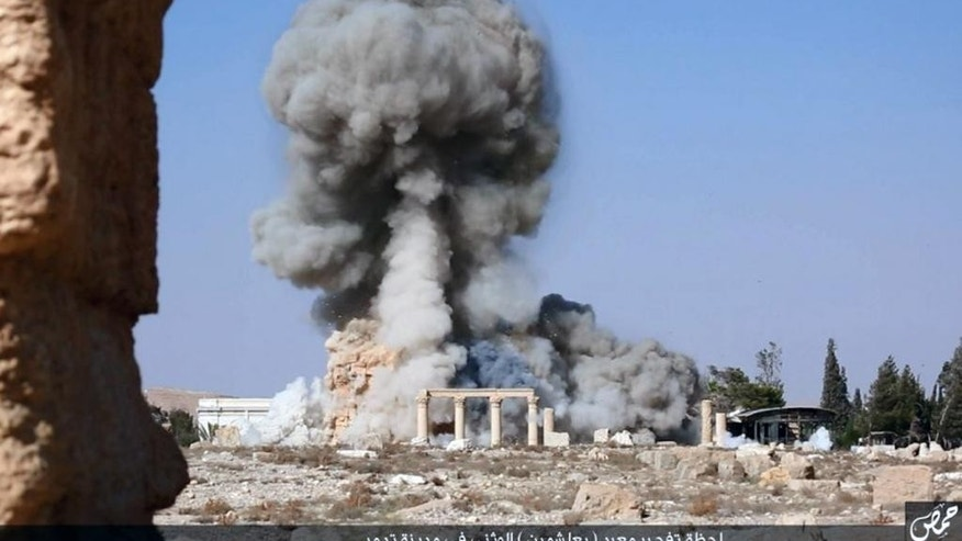 "FILE - This undated file photo released Tuesday, Aug. 25, 2015 on a social media site used by Islamic State militants, which has been verified and is consistent with other AP reporting, shows smoke from the detonation of the 2,000-year-old temple of Baalshamin in Syria's ancient caravan city of Palmyra. The nearly 2,000-year-old temple in the Syrian city of Palmyra this week was the latest victim in the Islamic State group's campaign of destruction of historic sites across the territory it controls in Iraq and Syria. Arabic at bottom reads, ""The moment of detonation of the pagan Baalshamin temple in the city of Palmyra."" (Islamic State social media account via AP, File)"