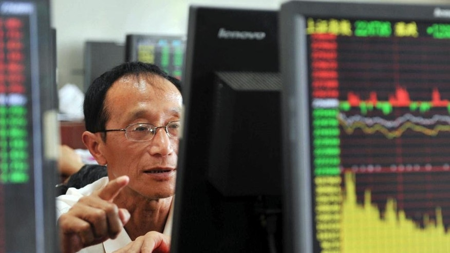 A Chinese stock investor monitors stock prices at a brokerage house in Hangzhou in eastern China's Zhejiang province Tuesday Aug. 25, 2015. China's stock market index tumbled for a fourth day, falling 7.6 percent Tuesday to an eight-month low.(Chinatopix via AP) CHINA OUT