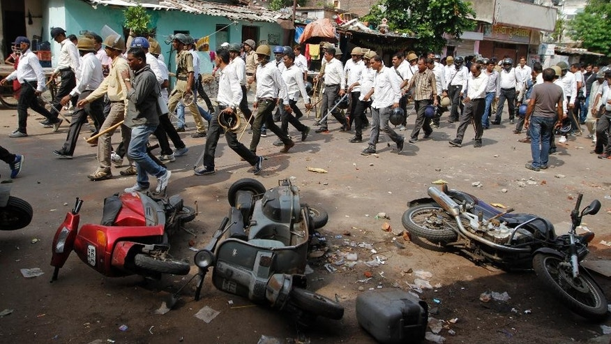 Indian policemen in plain clothes walk past vehicles damaged during a clash between two groups in Ahmadabad, India, Tuesday, Aug. 25, 2015. Clashes were reported in parts of the city after tens of thousands of members Gujarat's Patel community held a rally demanding affirmative action for better access to education and employment. (AP Photo/Ajit Solanki)