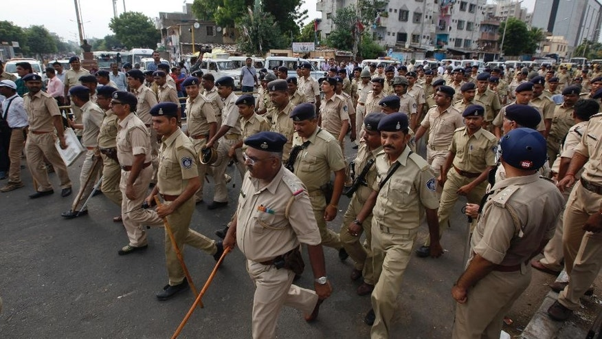 Indian policemen patrol after a clash between two groups in Ahmadabad, India, Tuesday, Aug. 25, 2015. Clashes were reported in parts of the city after tens of thousands of members Gujarat's Patel community held a rally demanding affirmative action for better access to education and employment. (AP Photo/Ajit Solanki)
