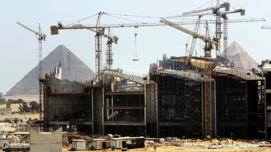 Cranes work at the site of Egypt's Grand museum, near the Giza Pyramids on the outskirts of Cairo, Egypt, Tuesday, Aug. 25, 2015. The massive new museum being built by the Pyramids is intended to house 100,000 ancient artifacts including King Tutankhamun's mummy. (AP Photo/Amr Nabil)
