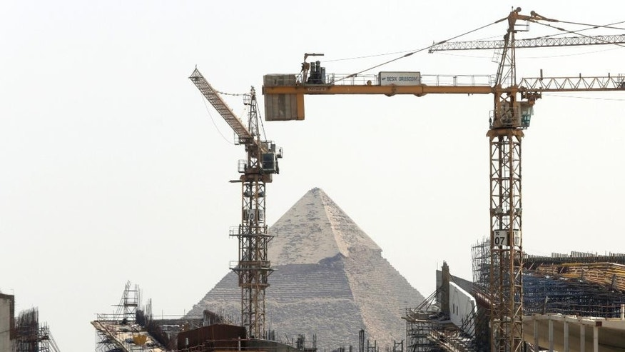 Cranes rise at the site of Egypt's Grand museum, near the historical site of the Giza Pyramids just outside of Cairo, Tuesday, Aug. 25, 2015. The massive new museum by the Pyramids is intended to house 100,000 ancient artifacts including King Tutankhamun's mummy. (AP Photo/Amr Nabil)