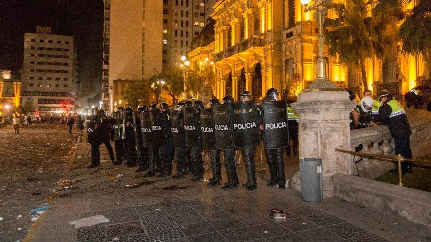 Police stand outside the government house during a protest by voters claiming fraud in the recent election for governor in Tucuman, Argentina, Monday, Aug. 24, 2015. The ruling party Frente Para la Victory's candidate Juan Manzur won Sunday's elections that were tarnished with allegations of malpractice and fraud. (Julio Pantoja/Infoto via AP)