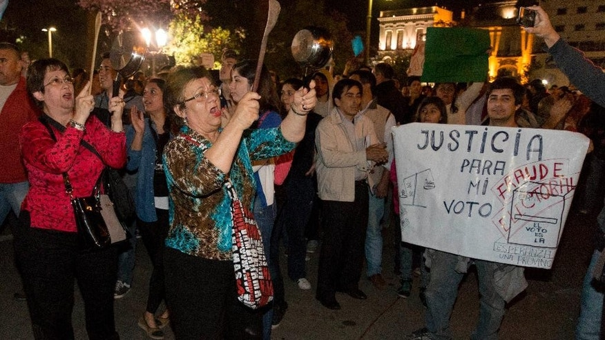 "Demonstrators bang pots to protest alleged fraud in the recent governorship election in Tucuman, Argentina, Monday, Aug. 24, 2015. The ruling party Frente Para la Victory's candidate Juan Manzur won Sunday's elections that were tarnished with allegations of malpractice and fraud. The sign reads in Spanish ""Justice for my vote."" (Julio Pantoja/Infoto via AP)"
