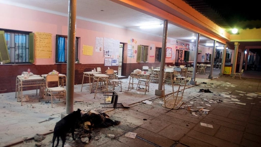 In this Sunday, Aug. 23, 2015 photo, a dog walks in a polling station after it was trashed by staunch supporters of various political parties during the provincial governorship election in San Pablo, Tucuman, Argentina. According to authorities, 40 ballot boxes were burned during an election in which the ruling party Frente Para la Victory's candidate Juan Manzur was declared winner. (Bruno Cerimele/Infoto via AP)