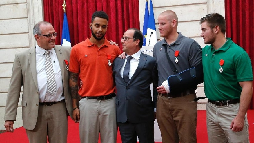 CORRECTS SADLER'S SCHOOL TO SACRAMENTO STATE UNIVERSITY, INSTEAD OF SACRAMENTO UNIVERSITY - From the left, British businessman Chris Norman, Anthony Sadler, a senior at Sacramento State University in California, French President Francois Hollande, U.S. Airman Spencer Stone, and Alek Skarlatos a U.S. National Guardsman from Roseburg, Ore., pose at the Elysee Palace, Monday, Aug. 24, 2015 in Paris, France. Hollande pinned the Legion of Honor medal on Stone, Skarlatos and Sadler, three long-time friends who subdued a gunman on Friday, Aug. 21, as he moved through a speeding train with an assault rifle strapped to his bare chest. Norman also jumped into the fray. (AP Photo/Michel Euler, Pool)