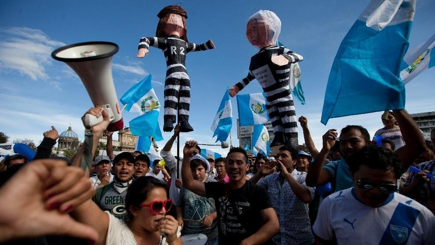 In this Saturday, Aug. 22, 2015 photo, demonstrators hold effigies representing Guatemala's President Otto Perez Molina, right, and former Vice President Roxana Baldetti, during a protest demanding the resignation of Perez Molina, outside the National Palace in Guatemala City. Baldetti was detained Friday in connection with a customs corruption scandal that led to her resignation in May, and prosecutors announced they are seeking to investigate Perez Molina in the matter. (AP Photo/Moises Castillo)