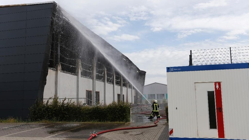 Firefighters spray water onto a gym intended as temporary housing for refugees that has burned to the ground in Nauen, west of Berlin, Germany, Tuesday, Aug. 25, 2015. (AP Photo/Ferdinand Ostrop)