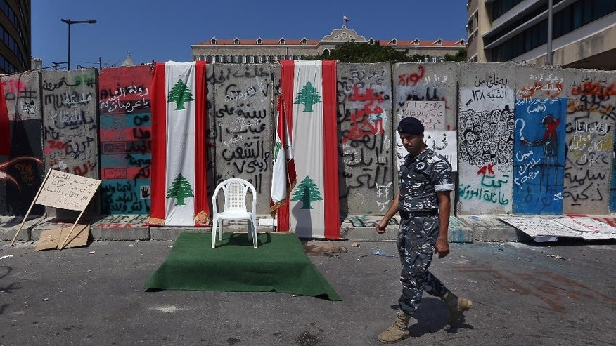 A Lebanese policeman passes by an empty chair, that protesters placed to represent the presidential vacuum, in front of a concrete wall installed by authorities near the main Lebanese government building, in downtown Beirut, Lebanon, Tuesday, Aug. 25, 2015. Anticipating more protests, authorities installed a concrete wall near the main Lebanese government building, site of the largest protests. On Saturday and Sunday nights, police fired tear gas and water cannons at the protesters, battling them in the streets of Beirut in dramatic clashes, wounding dozens. (AP Photo/Bilal Hussein)