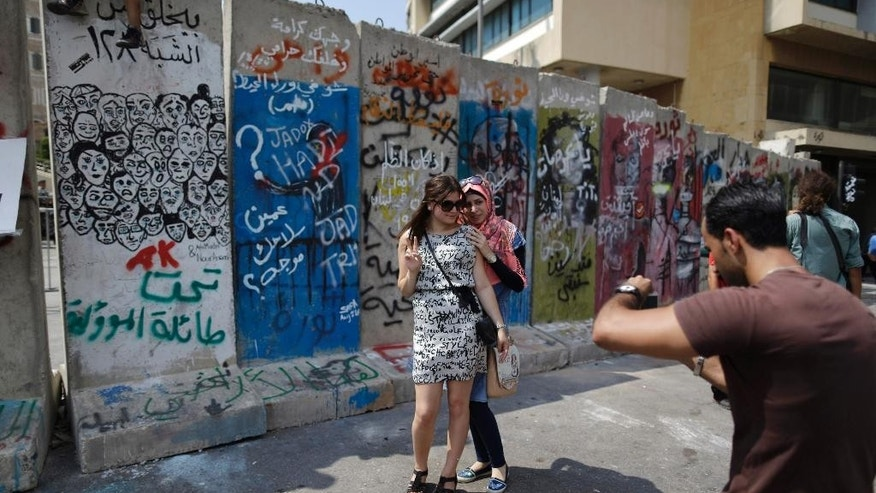 Lebanese women have their picture taken in front a concrete wall installed by authorities near the main Lebanese government building, in downtown Beirut, Lebanon, Tuesday, Aug. 25, 2015. Anticipating more protests, authorities installed a concrete wall near the main Lebanese government building, site of the largest protests. On Saturday and Sunday nights, police fired tear gas and water cannons at the protesters, battling them in the streets of Beirut in dramatic clashes, wounding dozens. (AP Photo/Hassan Ammar)