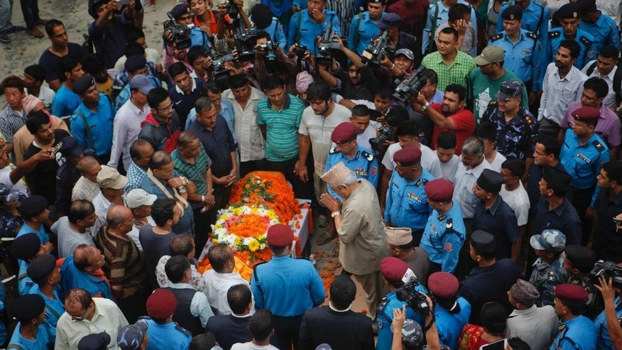 Nepalese Home Minister Bam Dev Gautam pays respect to Laxman Neupane, one among the police officers killed in Monday's clashes in western Nepal, after his body was brought to Kathmandu, Nepal, Tuesday, Aug. 25, 2015. Ethnic protesters, demanding statehood, attacked police with spears and knives a day earlier in western Nepal. (AP Photo/Niranjan Shrestha)