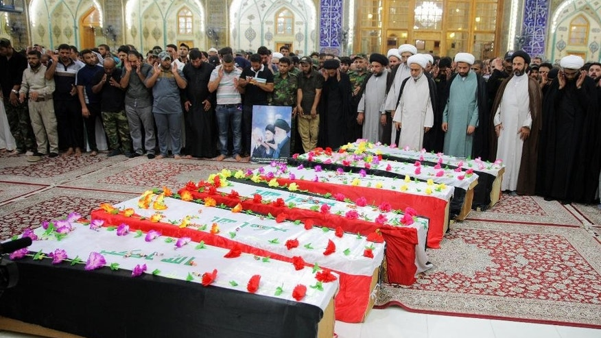 In this Sunday, Aug. 23, 2015 photo, mourners pray around the flag-draped coffins of six members of the Peace Brigades, a Shiite militia group loyal to Shiite cleric Muqtada al-Sadr, during their funeral procession inside the shrine of Imam Ali in Najaf, 100 miles (160 kilometers) south of Baghdad, Iraq. The militiamen were killed in Ramadi during fighting with Islamic State militants on Saturday, their families said. (AP Photo/ Jaber al-Helo)