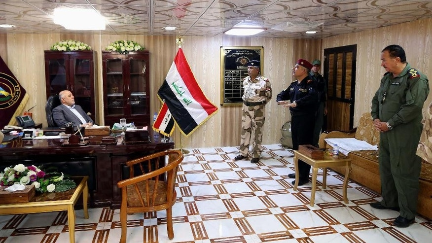 In this Monday, Aug. 24, 2015 photo, Iraq's Prime Minister Haider al-Abadi, left, meets with his military commanders at an Iraqi Army base  near the oil refinery town of Beiji north of Baghdad, Iraq. Al-Abadi said that winning the ongoing battle over control of an oil refinery town north of Baghdad is the key to defeating the Islamic State group in Iraq during his visit to the town of Beiji. (AP Photo)