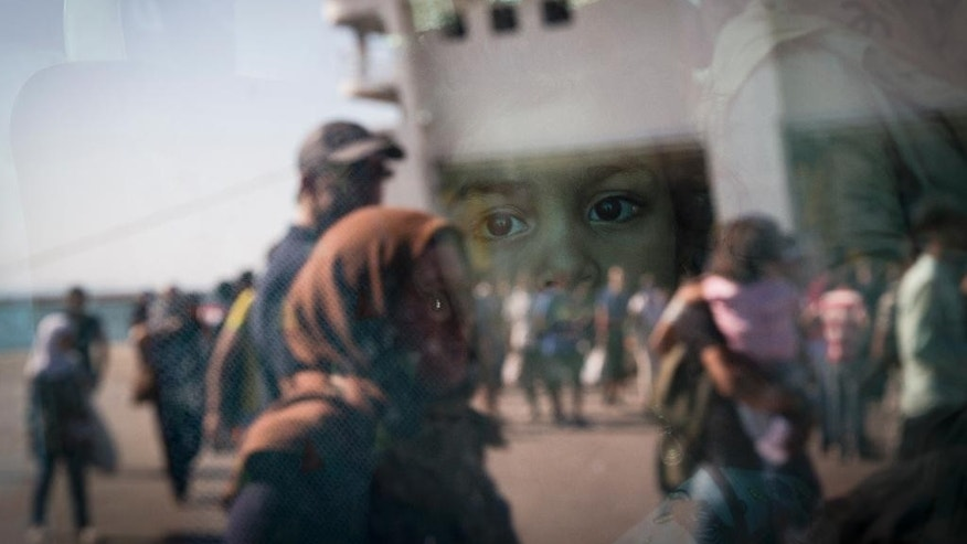 A little girl from Syria looks out of a bus as the ferry she arrived in is reflected in the bus window at the port of Piraeus, Greece, Tuesday, Aug. 25, 2015. About 2,400 Syrian refugees  stranded on Lesbos _ which they reached in small boats from nearby Turkey _ due to a dearth of ferry tickets in the high holiday season, were on the ferry. Greece has been overwhelmed this year by record numbers of migrants. (AP Photo/Petros Giannakouris)