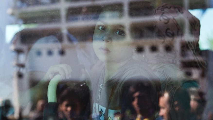 Syrian children look out of a window of a bus after they arrived in  a ferry at Athens' port of Piraeus, on Tuesday, Aug. 25, 2015. About 2,400 Syrian refugees  stranded on Lesbos _ which they reached in small boats from nearby Turkey _ due to a dearth of ferry tickets in the high holiday season were on the ferry. Greece has been overwhelmed this year by record numbers of migrants. (AP Photo/Petros Giannakouris)