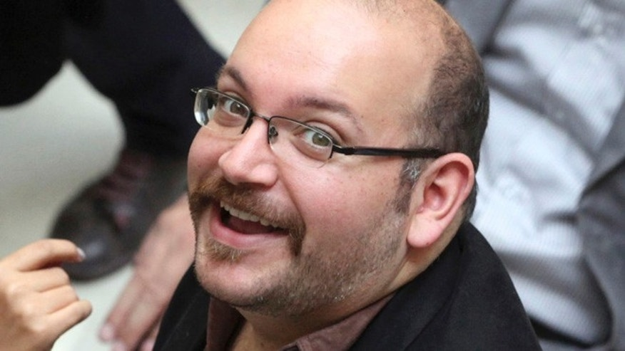 FILE 2013: Jason Rezaian, an Iranian-American correspondent for the Washington Post, smiles as he attends a presidential campaign of President Hassan Rouhani in Tehran.