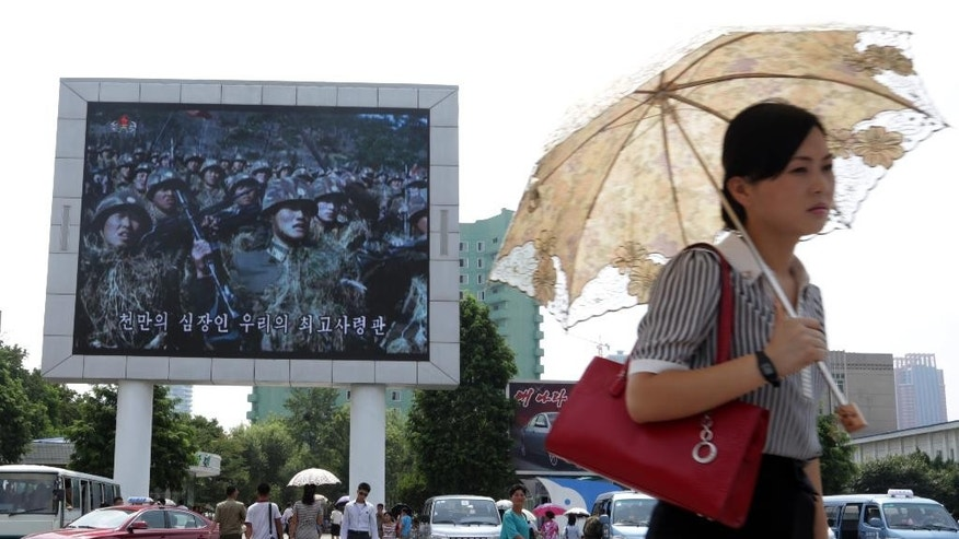 In this Friday, Aug. 21, 2015 photo, a woman walks past a propaganda movie shown on a large screen in Pyongyang, North Korea. North Koreans are accustomed to being told they are on the brink of war with their southern neighbors and U.S. troops, and as talks with South Korea in the truce village of Panmunjom dragged on this weekend one had to look hard in the North Korean capital of Pyongyang to find signs of a brewing crisis. (AP Photo/Dita Alangkara)