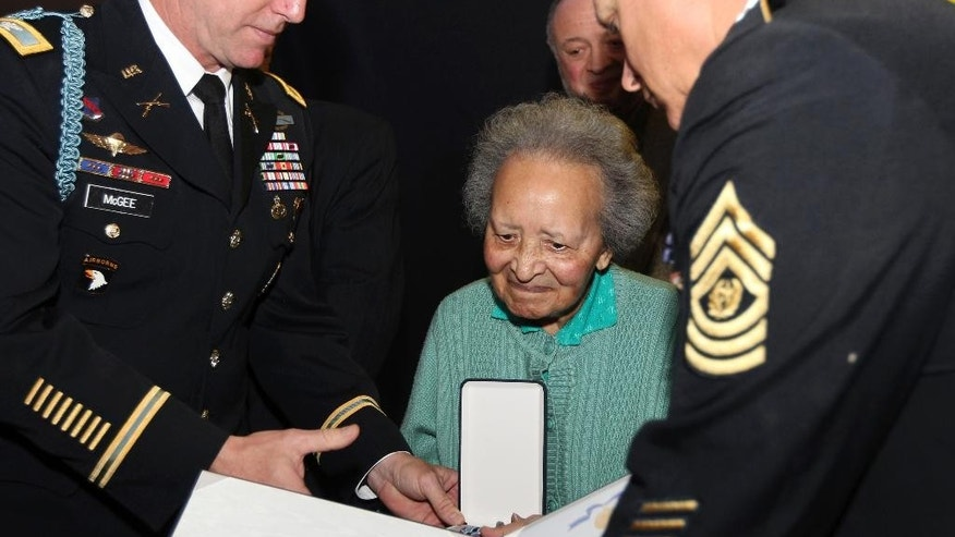 FILE - In this Monday, Dec. 12, 2011 file photo, Belgian nurse Augusta Chiwy, center, receives an award for valor from the U.S. Army, in Brussels. Chiwy who helped save hundreds of American soldiers during the Battle of the Bulge at the end of World War II has died, she was 94. A service of burial will be held in the town of Bastogne, southeast Belgium on Saturday, Aug. 29, 2015. (AP Photo/Yves Logghe, File)