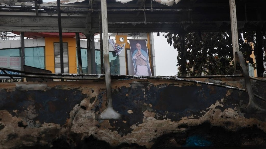 A poster of Indian freedom fighter and India's first home minister Sardar Vallabhbhai Patel is seen through a bus damaged during clashes in Ahmadabad, India, Wednesday, Aug. 26, 2015. Authorities issued a curfew Tuesday night in at least five cities in Gujarat state, after mobs attacked police officers with stones and sticks and burned government and private vehicles.(AP Photo/Ajit Solanki)