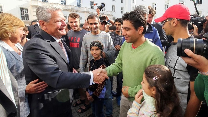 President Joachim Gauck visits a asylum-seekers home in  Berlin-Wilmersdorf and welcomes refugees in Berlin, Germany, Wednesday Aug. 26,  2015. German President Joachim Gauck and Chancellor Angela Merkel were visiting asylum seeker homes Wednesday to express support for refugees following an outburst of anti-foreigner violence over the weekend.  Merkel planned to meet with refugees, aid workers and local officials at a shelter in Heidenau, near Dresden, that had been at the center of neo-Nazi riots. (Wolfgang Kumm /dpa via AP)