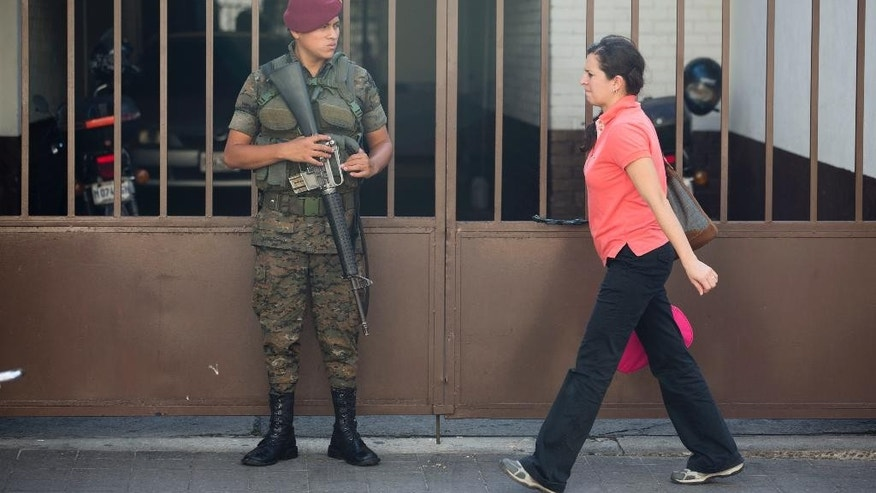 A Guatemalan soldier stands guard in front of the Presidential House in Guatemala City, Tuesday, Aug. 25, 2015. The Supreme Court took the first step in allowing impeachment proceedings against Guatemalan President Otto Perez Molina in a fraud scandal that is pushing the country into political crisis. (AP Photo/Moises Castillo)