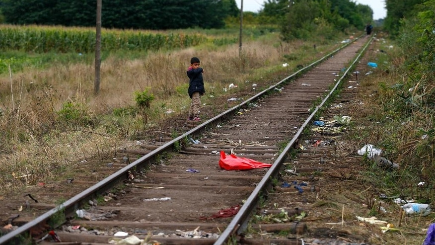 A migrant boy stands on the railway close to the Serbian border with Hungary, near Horgos, Serbia, early Wednesday, Aug. 26, 2015. The rush over the border by migrants fleeing war and poverty in the Middle East, Africa and Asia followed Macedonia's decision to lift a three-day blockade of its border with Greece after thousands of migrants simply stormed past the Macedonian police who tried to stop them with force. (AP Photo/Darko Vojinovic)