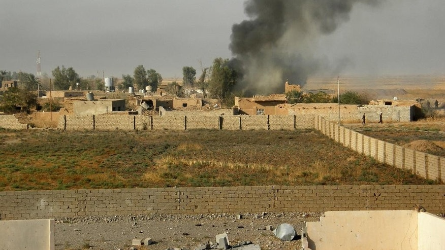 Smoke rises from extremist positions during a military operation to regain control of some villages from Islamic State group fighters, south of oil-rich city of Kirkuk, 180 miles (290 kilometers) north of Baghdad, Iraq, Wednesday, Aug. 26, 2015. (AP Photo)