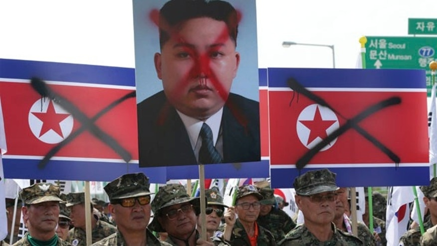 Aug. 13, 2015: Members of the Korean Disabled Veterans Association hold mock North Korean flags and a defaced image of North Korean leader Kim Jong Un during a rally denouncing North Korea in front of the Unification Bridge near the border village of Panmunjom, South Korea. (AP Photo/Lee Jin-man)