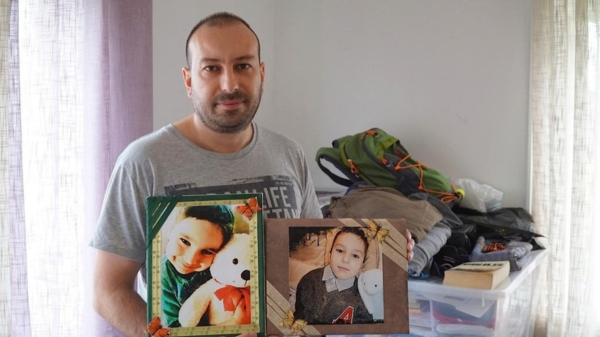 In this photo taken Friday, May 11, 2015, Feridun Mustafaoglu  hold pictures of his children  in his small one-room rental during an interview with The Associated Press, in Stavanger, Norway. Mustafaoglu helped his wife and two sons flee to Turkey after a tip-off that Norwegian child protection services were about to take custody of the children. After a series of highly charged custody disputes, Norway now faces accusations of cultural insensitivity at best and child theft at worst, as increasing numbers of immigrant children are being seized by officials and handed over to Norwegian foster families. (AP Photo/David Keyton)