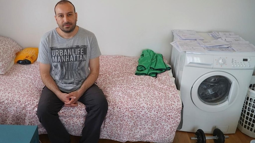 In this May 11, 2015, photo, Feridun Mustafaoglu sits alone in his small one-room rental during an interview with The Associated Press, in Stavanger, Norway. Mustafaoglu helped his wife and two sons flee to Turkey after a tip-off that Norwegian child protection services were about to take custody of the children. After a series of highly charged custody disputes, the oil-rich Norway now faces accusations of cultural insensitivity at best and child theft at worst, as increasing numbers of immigrant children are being seized by officials and handed over to Norwegian foster families. (AP Photo/David Keyton)