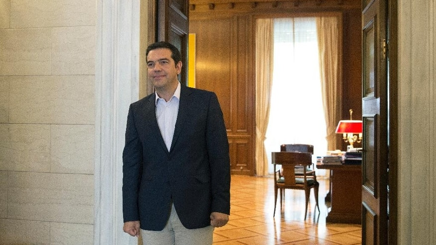 Outgoing Greek Prime Minister Alexis Tsipras stands outside his office during the arrival of the Archbishop of Albania in Athens, Tuesday, Aug. 25, 2015. Tsipras resigned on Thursday, Aug. 20, following a rebellion in his party over Greece's new bailout, which saw dozens of Syriza lawmakers dissent when the deal came to a vote in Parliament. (AP Photo/Petros Giannakouris)
