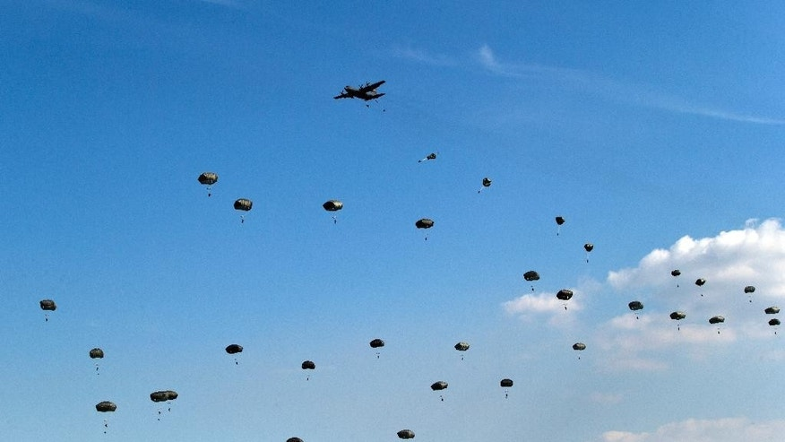 US paratroopers with the 18th Airborne Corps jump out of an airplane during the Swift Response 15 air exercise, the largest airborne training event in Europe since the end of the Cold War, at the Smardan training range in eastern Romania, Wednesday, Aug. 26, 2015. More than 200 paratroopers from Italy, Spain, and the U.S. have taken part in a parachute assault at a shooting range in eastern Romania, part of a month of exercises to demonstrate NATO's capacity to rapidly deploy and operate. (AP Photo/Vadim Ghirda)