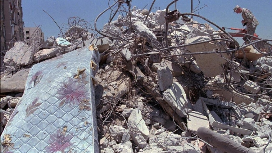 FILE - In this June 27, 1996 file photo, a U.S. Air Force officer climbs a pile of rubble to photograph the devastated building in Dhahran, Saudi Arabi where a truck bomb destroyed the eight story building behind Tuesday and killed 19 U.S. servicemen, injuring hundreds.  A man suspected in the 1996 bombing of the Khobar Towers residence at a U.S. military base in Saudi Arabia has been captured, a U.S. official tells The Associated Press. Ahmed al-Mughassil , described by the FBI in 2001 as the head of the military wing of Saudi Hezbollah, is suspected of leading the attack that killed 19 U.S. service personnel and wounded almost 500 people.(AP Photo/Greg Marinovich, File)