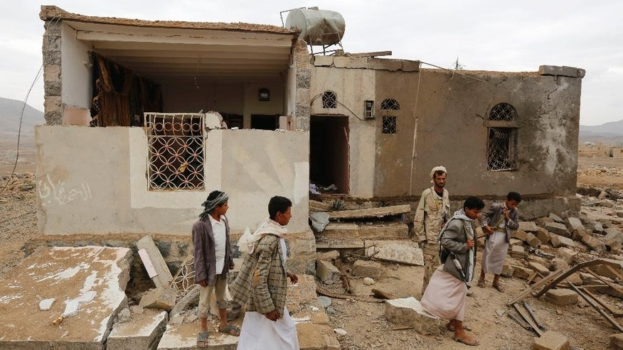 Shiite rebels known as Houthis stand near a house destroyed by a Saudi airstrike in Sanaa, Yemen, Wednesday, Aug. 26, 2015. (AP Photo/Hani Mohammed)