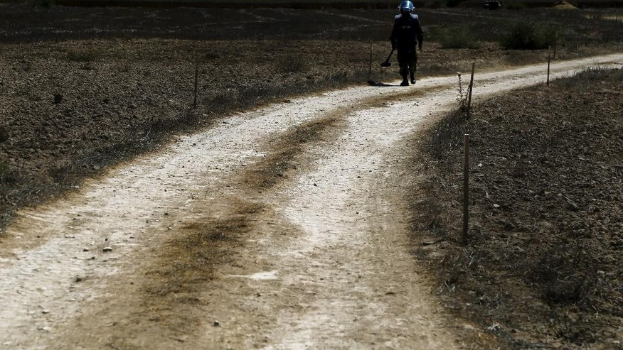 A U.N. Cambodian specialist of  mine detecting e team walks at a dirt road during a demining demonstration in the U.N. buffer zone (Green Line) near the Mammari village between the Greek and Turkish Cypriot controlled areas outside of the divided capital Nicosia, Cyprus, Wednesday, Aug. 26, 2015. United Nations officials say a 17,000 square meter parcel of farmland situated inside a no man's land in ethnically divided Cyprus is now clear of land mines and will be returned for grazing and cultivation.  (AP Photo/Petros Karadjias)