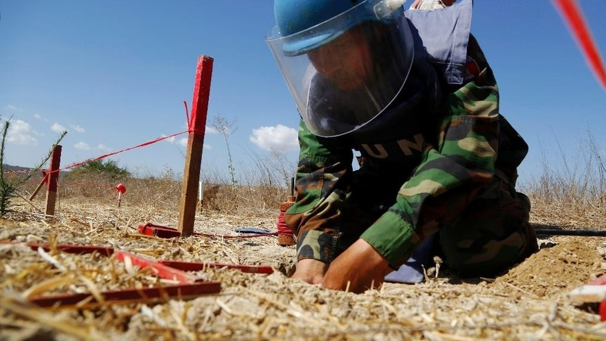 A U.N. Cambodian specialist from a  demining team uses mine detecting device during a demining demonstration in the U.N. buffer zone (Green Line) near the Mammari village between the Greek and Turkish Cypriot controlled areas outside of the divided capital Nicosia, Cyprus, Wednesday, Aug. 26, 2015. United Nations officials say a 17,000 square meter parcel of farmland situated inside a no man's land in ethnically divided Cyprus is now clear of land mines and will be returned for grazing and cultivation. (AP Photo/Petros Karadjias)