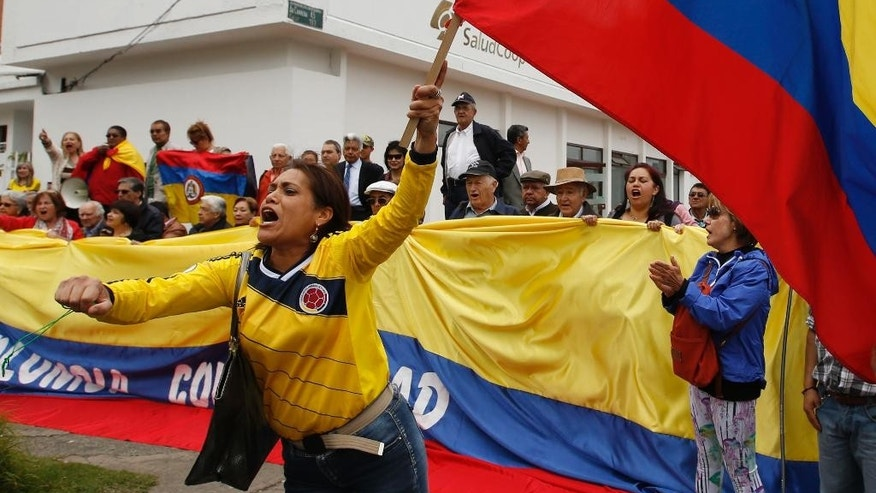 A colombians woman shouts in front of the Venezuelan consulate to protest Venezuela's border crackdown, in Bogota, Colombia, Wednesday, Aug. 26, 2015. The two nations' foreign ministers met in Colombia Wednesday, to try to cool tensions roused when Venezuelan President Nicolas Maduro closed a major border crossing, declared a state of emergency in six western cities and deported more than 1,000 Colombian migrants. (AP Photo/Fernando Vergara)