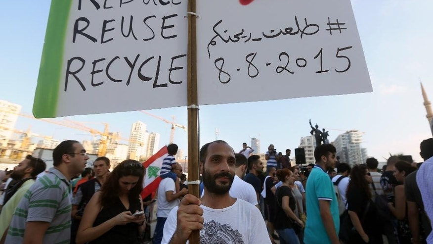 "FILE - In this Saturday, Aug. 8, 2015, file photo, a Lebanese protester holds a placard in Arabic thats reads ""You Stink,"" during a demonstration against the ongoing trash crisis, at the Martyrs square in downtown Beirut, Lebanon. Starting out as a small group of tech-savvy young activists who organized to protest the garbage that for weeks has been piling up on Beirut's streets, Lebanon's ""You Stink"" movement has now grown into a popular uprising that seeks to nip at the power base of an entire political class. (AP Photo/Bilal Hussein, File)"