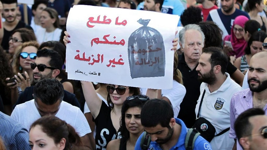 "FILE - In this Saturday, Aug. 8, 2015, file photo, a Lebanese protester chants slogans against the Lebanese government during a demonstration against the ongoing trash crisis, at the Martyrs square in downtown Beirut, Lebanon. Her placard in Arabic read: ""We got nothing from you but garbage."" Starting out as a small group of tech-savvy young activists who organized to protest the garbage that for weeks has been piling up on Beirut's streets, Lebanon's ""You Stink"" movement has now grown into a popular uprising that seeks to nip at the power base of an entire political class. Arabic on sign reads: 'Nothing comes from you but garbage'. (AP Photo/Bilal Hussein, File)"