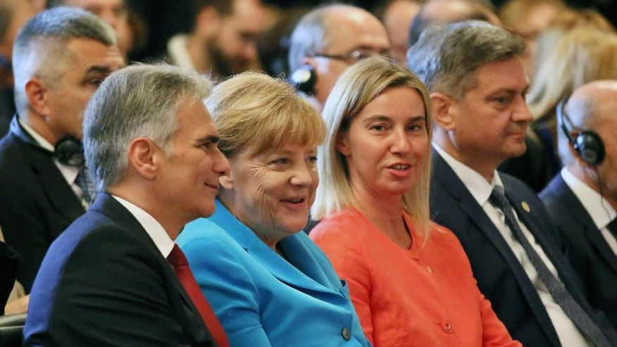 Austrian Chancellor Werner Faymann, German Chancellor Angela Merkel, European Union foreign policy chief Federica Mogherini and Bosnian Prime Minister Denis Zvizdic, from left, listen to a speech at the start of the Western Balkans Summit in the Hofburg palace in Vienna, Austria, Thursday, Aug 27, 2015. (AP Photo/Ronald Zak)