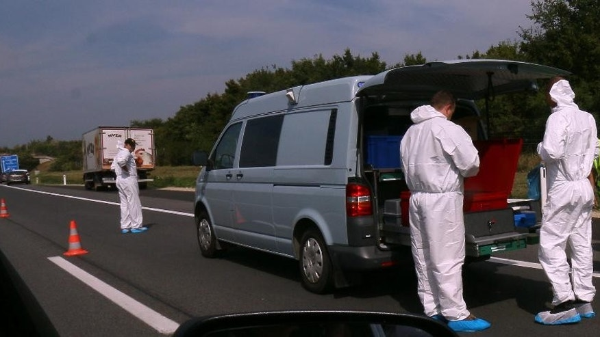 Police stand in fron of a truck parked on the shoulder of the highway A4 near Parndorf south of Vienna, Austria, Thursday, Aug 27, 2015. At least 20 migrants were found dead in the truck parked on the Austrian highway leading from the Hungarian border, police said. (AP Photo/Ronald Zak)