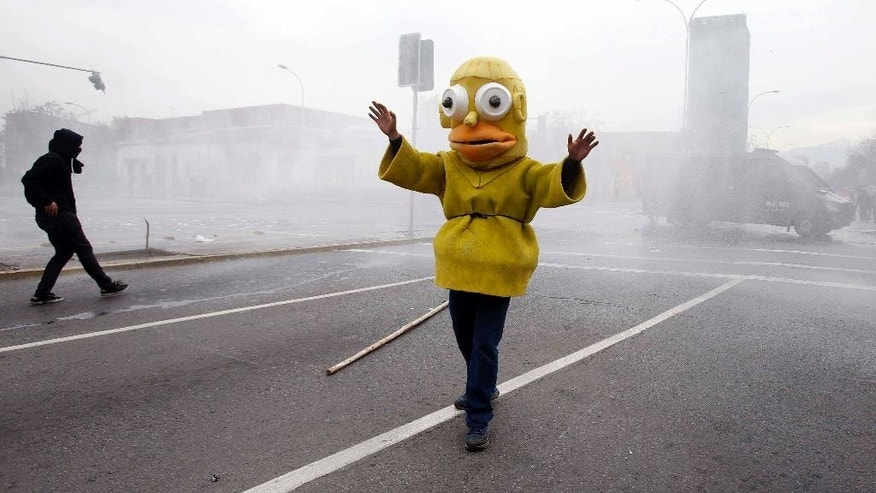 A protester dressed as the cartoon character Homer Simpson steps between demonstrators and police, in an attempt to stop clashes at the end of a student march in Santiago, Chile, Thursday, Aug. 27, 2015. Demonstrators came out to complain about delays in an education overhaul and ask President Michelle Bachelet to fulfill her campaign promise of free education. (AP Photo/Luis Hidalgo)