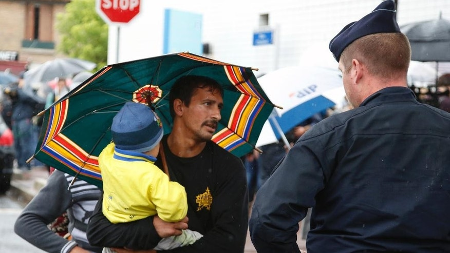 A Roma, also known as Gypsy, carrying his child, argues with French police officer as police dismantle sprawling Roma camp in La Courneuve, on Paris outskirts, France, Thursday, Aug. 27, 2015. Police are clearing out one of France's biggest and oldest Roma camps, a sprawling network of makeshift shelters that has housed about 200-300 people for at least three years, mostly from eastern Europe. (AP Photo/Francois Mori)