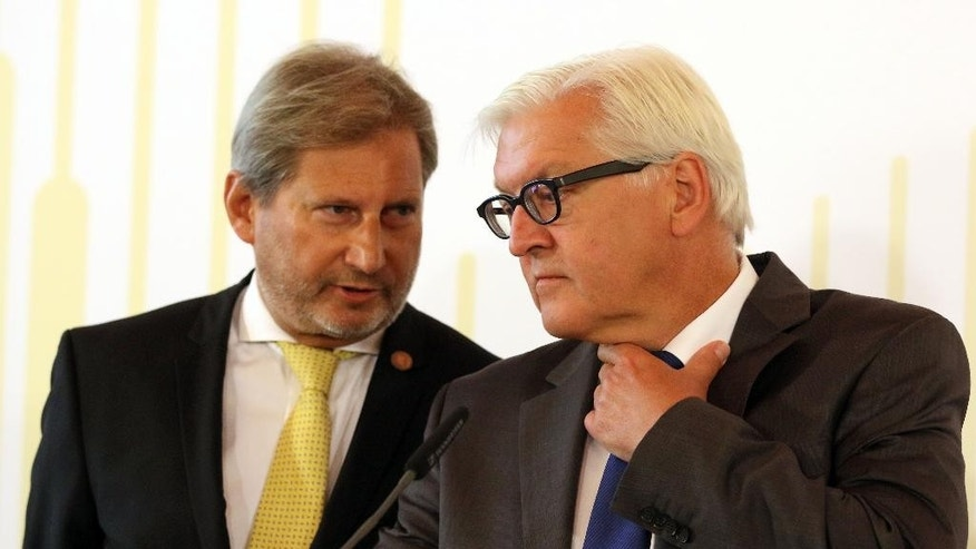 European Neighborhood Policy & Enlargement Negotiations commissioner Johannes Hahn and German Foreign Minister Frank-Walter Steinmeier, from left, talk during a press conference at the Western Balkans Summit at the Hofburg palace in Vienna, Austria, Thursday,  Aug.  27, 2015. (AP Photo/Ronald Zak)