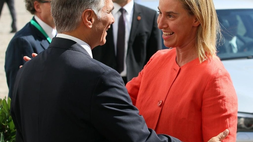 Austrian Chancellor Werner Faymann , left, welcomes European Union foreign policy chief Federica Mogherini,  for the start of the Western Balkans Summit at the Hofburg palace in Vienna, Austria, Thursday, Aug.  27, 2015. (AP Photo/Ronald Zak)