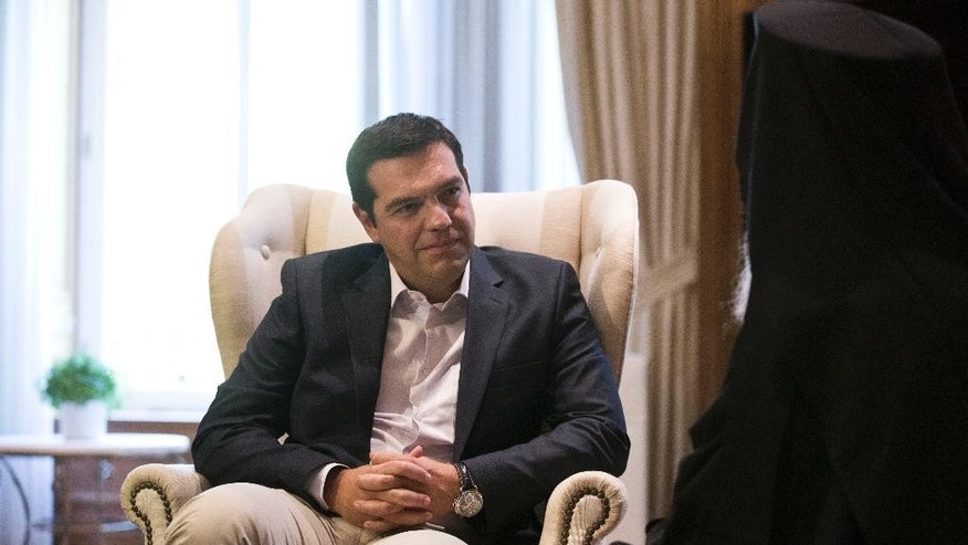 Outgoing Greek Prime Minister Alexis Tsipras listens to the Archbishop of Albania during their meeting in Athens, Tuesday, Aug. 25, 2015. Tsipras resigned on Thursday, Aug. 20 following a rebellion in his party over Greece's new bailout, which saw dozens of Syriza lawmakers dissent when the deal came to a vote in Parliament. (AP Photo/Petros Giannakouris)
