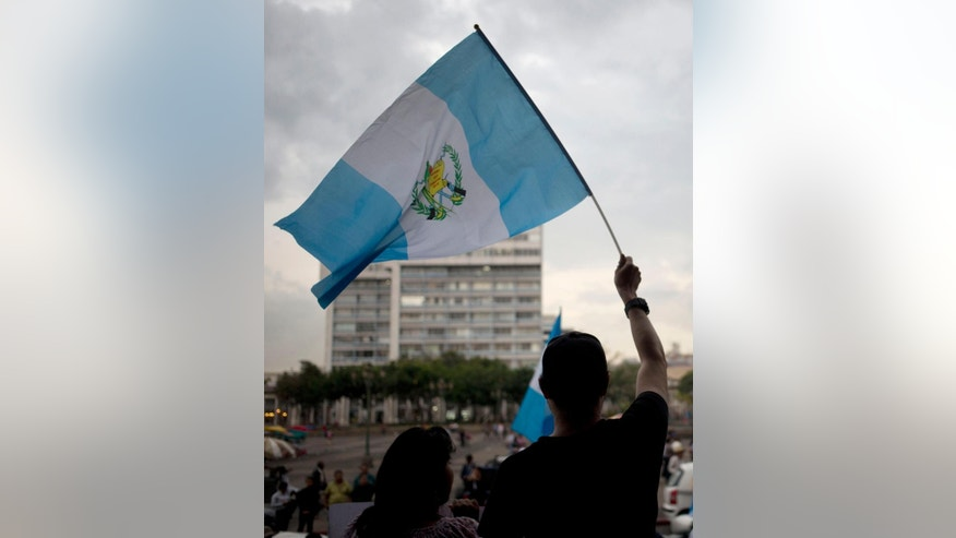 A man waves a Guatemalan flag during a demonstration demanding the resignation of Guatemala's President Otto Perez Molina, in front of the National Palace in Guatemala City, Wednesday, Aug. 26, 2015. About two dozen highway blockades were set up around the country by protesters demanding the president's resignation and that the Sept. 6 vote for his successor be postponed. He has vowed to stay on. (AP Photo/Moises Castillo)