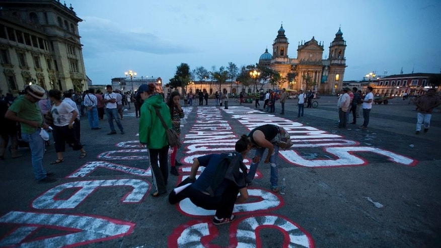 People paint a message on the ground demanding the resignation of Guatemala's President Otto Perez Molina, in front of the National Palace in Guatemala City, Wednesday, Aug. 26, 2015. About two dozen highway blockades were set up around the country by protesters demanding the president's resignation and that the Sept. 6 vote for his successor be postponed. He has vowed to stay on. (AP Photo/Moises Castillo)
